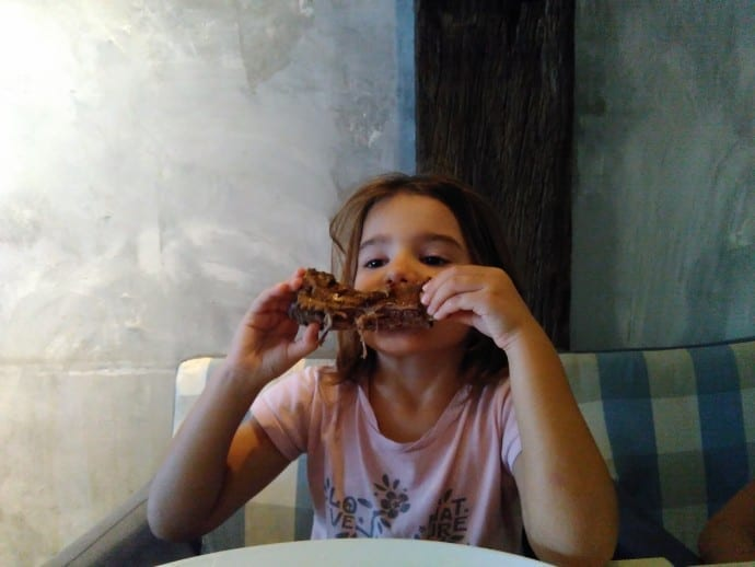Little girl gnawing on Wagyu rib.